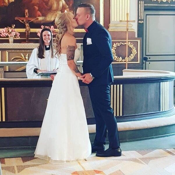 Bröllopspar som kysser varandra i kyrkan