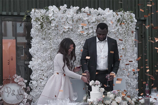 Vackert bröllopspar som skär i bröllopstårtan som är beställd från CakeByMelina i Norrköping