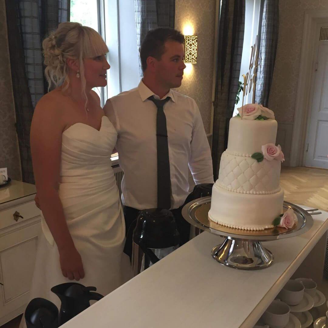 Bröllopspar som strax ska skära i Bröllopstårta från CakeByMelina i Norrköping
