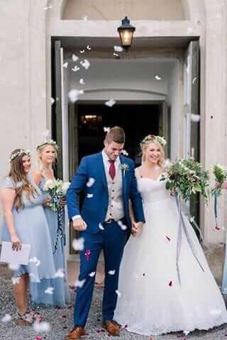 Stiligt bröllopspar som stegar ut från kyrkan