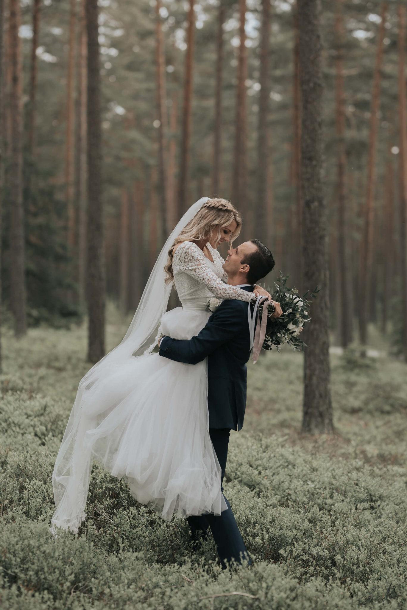 Bröllopspar som kramar om varandra i skogen
